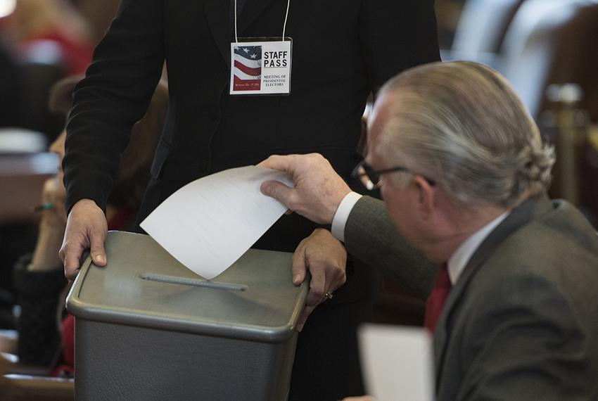 An elector casts his vote for President of the United States during the Electoral College meeting at the Texas Capitol on De…