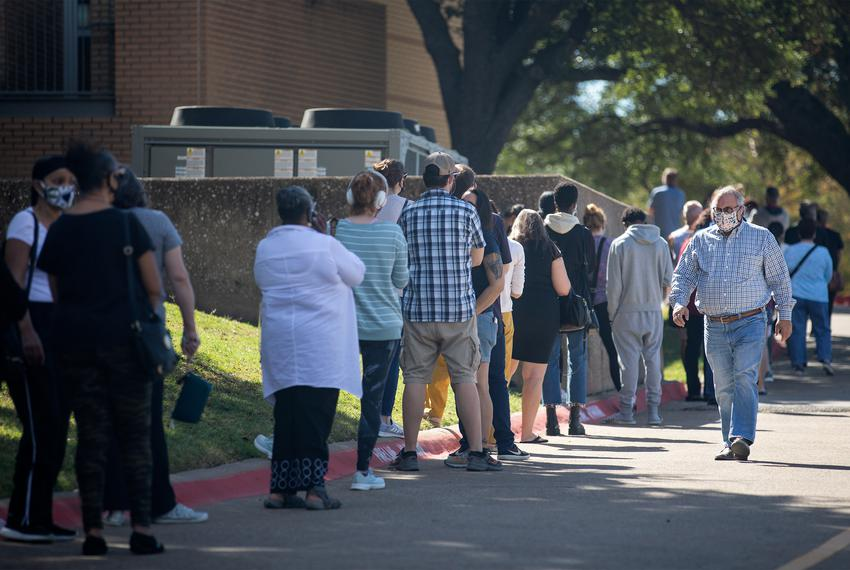 People wait in line to vote at Audelia Road Branch Library on the first day of early voting in Dallas on Oct. 13, 2020.