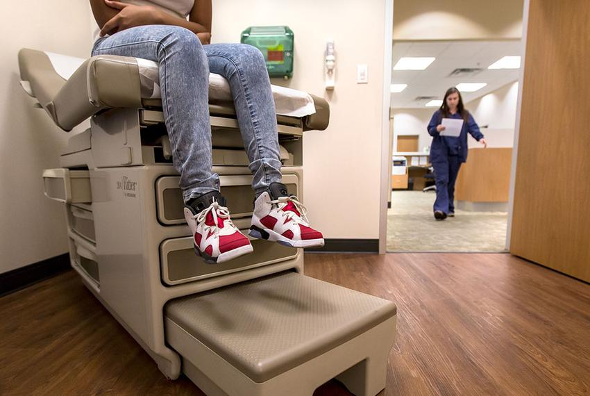 Eighth-grader Montanique DeShay waits as Ashlyn Brooks, medical assistant at MedSpring Urgent Care in Austin, comes to check…