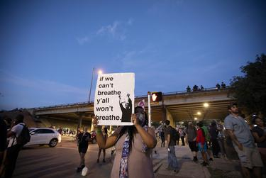 A protester holds a sign at a rally for George Floyd and Mike Ramos at Austin Police headquarters on May 30, 2020.