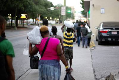 A group of migrants mostly from Africa walk a few blocks on June 26, 2019 from a makeshift processing center in downtown San Antonio to a shelter where they will spend the night. The shelter is run by the Interfaith Welcome Coalition.