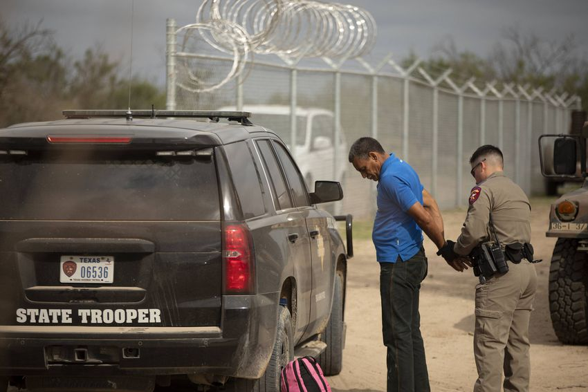 A Texas Department of Public Safety official arrests Nerio, a Venezuelan migrant, near the U.S. and Mexico border in Del Rio…