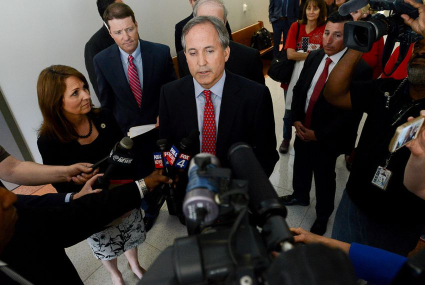 Texas Attorney General Ken Paxton, accompanied by his wife, Angela, left, speaks to the media after leaving the Fifth Court of Appeals on May 12, 2016 in Dallas.