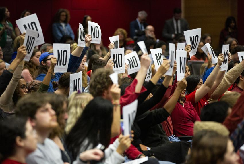 "Students raise papers printed ""NO,"" disagreeing with a panelist's answers during the Open Dialogue with UT Leadership abou..."