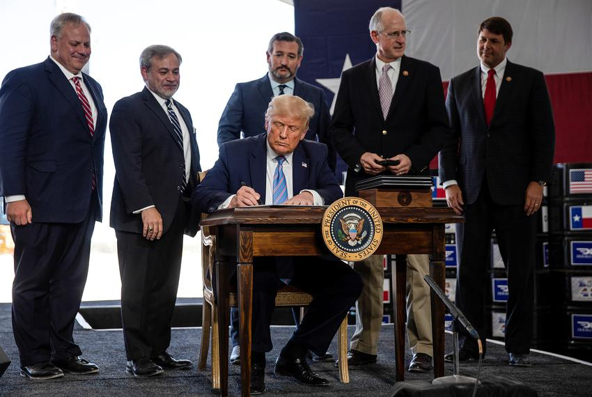 U.S. President Donald Trump signs presidential permits for energy development during a tour of the Double Eagle Energy Oil R…