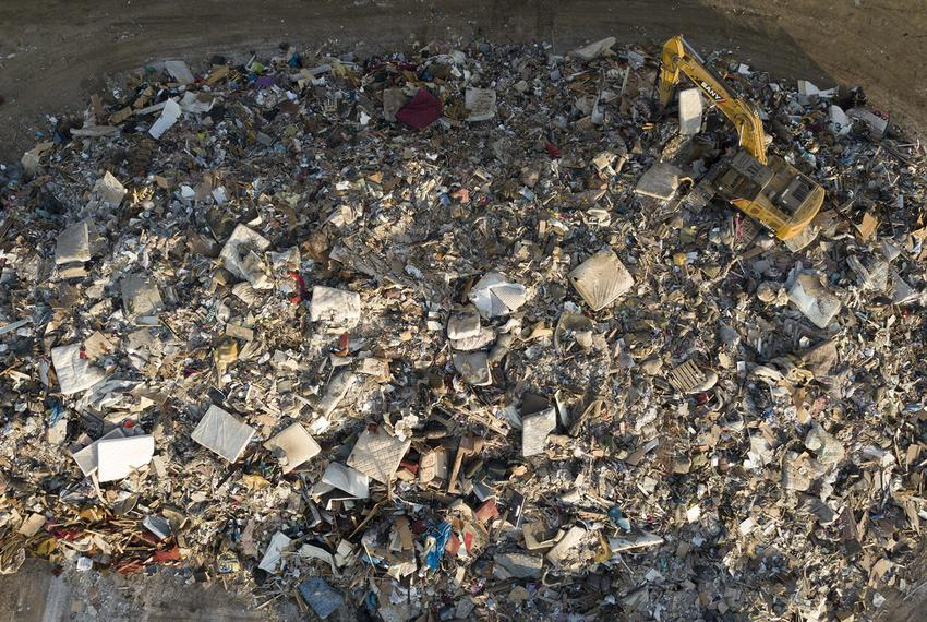 A digger sits on top of a growing city-run debris pile filled with water-damaged items, from mattresses to sheetrock, in Por…
