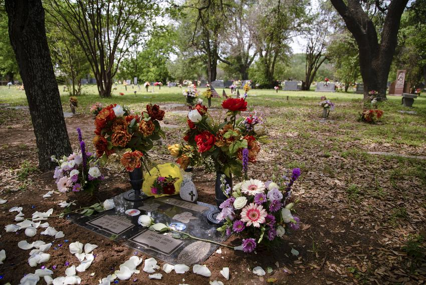 Flowers adorn the graveside of Michael Ramos at Assumption Cemetery in Austin, on April 19, 2021.  Ramos was shot and killed…