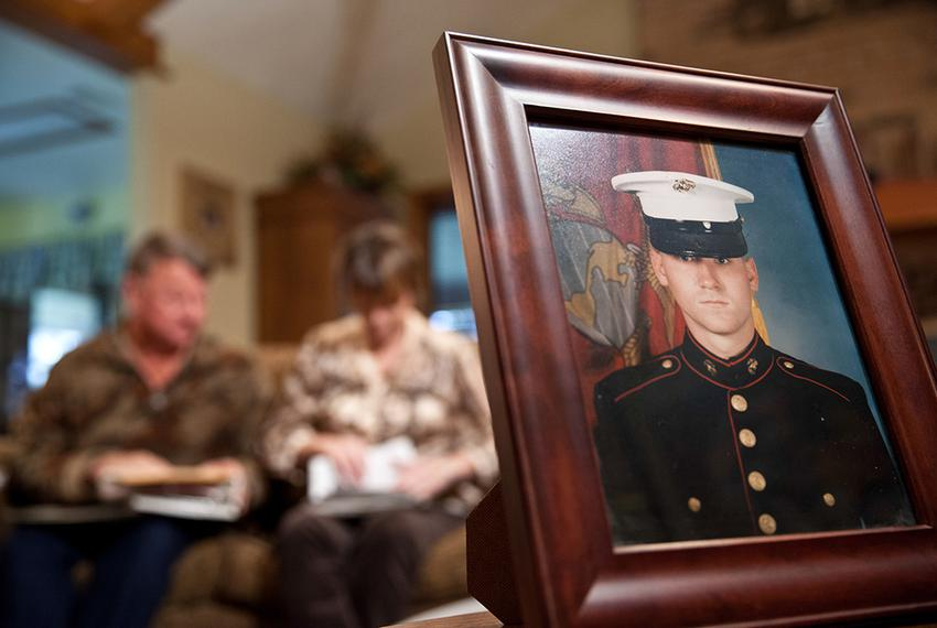 Dennis and Patty Thuesen look through photos of their son John from his childhood and his service in the military. John, an …