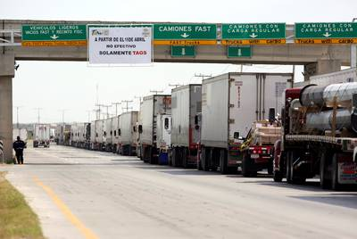 Tractor-trailers wait in a long line to cross into U.S. at the World Trade Bridge in Nuevo Laredo, Mexico on April 2, 2019.