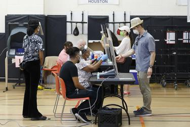 Voters check in with poll workers seated behind glass shields at the Metropolitan Multiservices Center in Houston for the delayed primary runoff election on Tuesday, July 14, 2020.