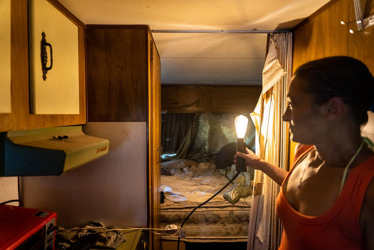 Susan shows me the bed where her and Donald sleep at night, lit by a light bulb plugged into an extension chord, the only light source in the trailer.