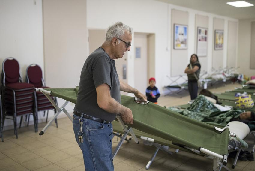 Eduardo Talamantes, a Navy veteran, helps set up cots at a migrant shelter at the Catholic Diocese of El Paso's main campu...