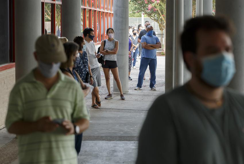 Voters, wearing masks and spread six feet apart, line up outside the Metropolitan Multiservice Center in Houston to vote i...