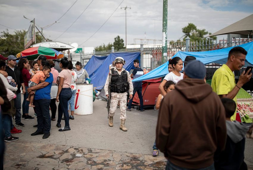 A Mexican soldier patrols a makeshift migrant camp at the base of Paso del Norte International Bridge in Ciudad Juarez.