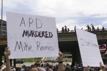 Protesters hold signs in response to the recent deaths of George Floyd and Mike Ramos.