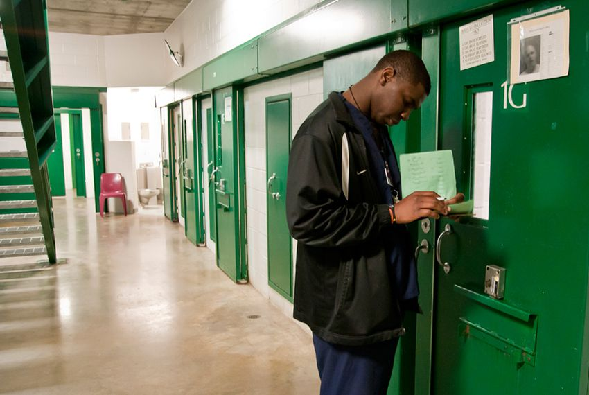 Christopher Ajayi, a psychiatric technician, makes his rounds at the Harris County Jail.