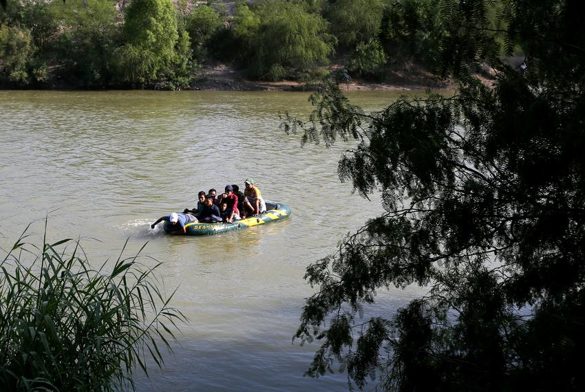 A suspected smuggler uses his arms to paddle a raft of immigrants across the Rio Grande in an illegal crossing of the Mexi...