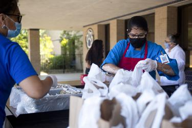 Round Rock ISD food service worker Hema Patel prepares meals to distribute to families during a curbside meal distribution at Bluebonnet Elementary School on Aug. 20, 2020 in Round Rock.