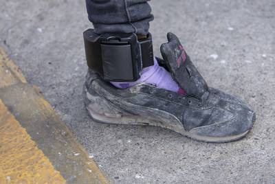 An immigrant at a bus station in McAllen shows her ankle monitor.