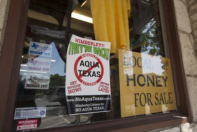 Businesses along the square in Wimberley show their opposition to turning over any portion of the City of Wimberley's wastewater treatment project to Aqua Texas.