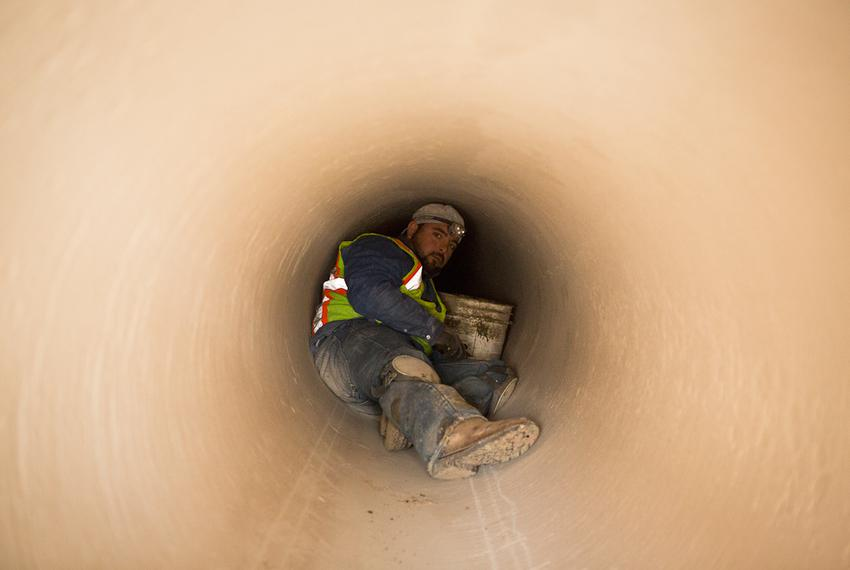 A water pipeline crew member waits for the joining of two sections of pipe in order to secure their connection internally.