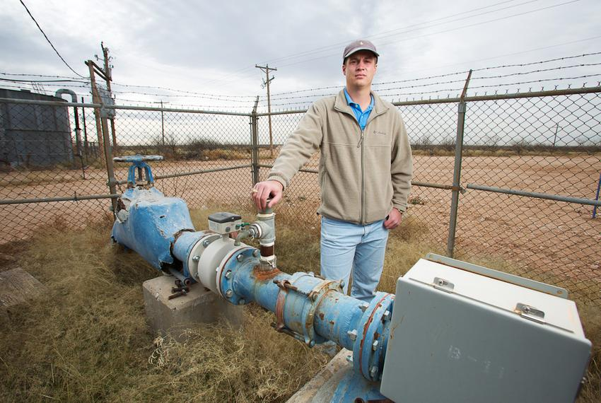 Kyle Krueger, a staff engineer with the Colorado River Municipal Water District, stands next to an older water well on land …