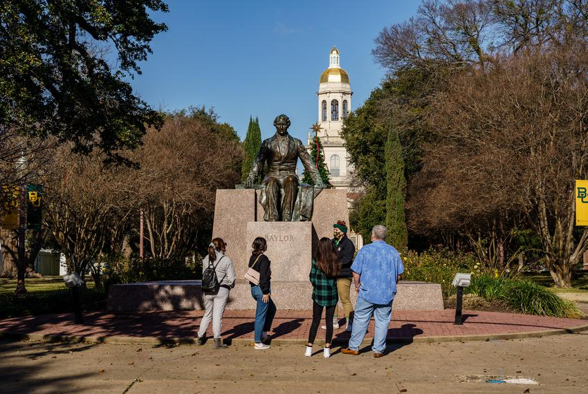 A group of prospective students takes an official campus tour in front of the statue of Judge Baylor at Baylor University in…