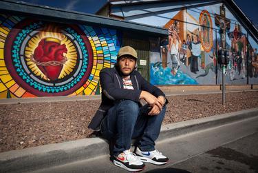 Juan Paul Flores Vazquez stands in front a mural in Segundo Barrio in El Paso. Flores is a DACA recipient.
