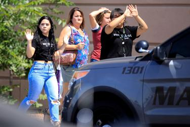 Showing their hands to police, shoppers evacuate Cielo Vista Mall after a mass shooting at a Walmart in El Paso on August 3, 2019.