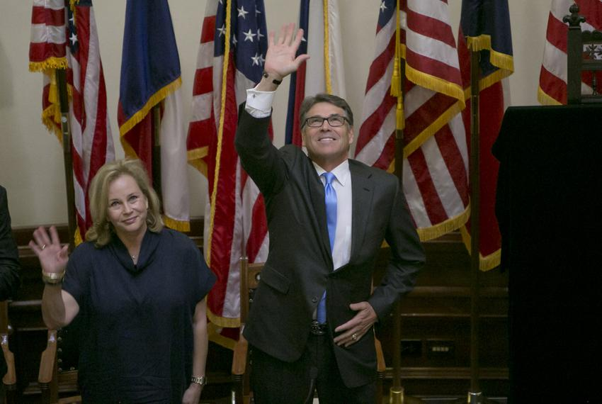 Gov. Rick Perry, waves to the crowd during the unveiling ceremony of his official portrait inside the Capitol rotunda on May…