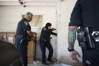 Travis County Deputies Juan Arispe and Theresa Stewart enter a home in Southwest Austin, where residents had been evicted.