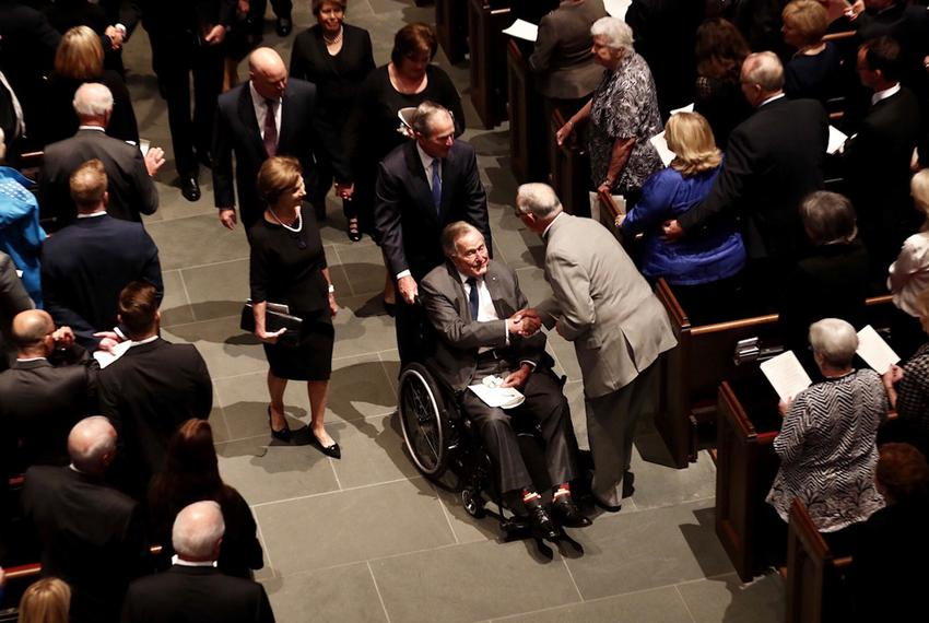Pushed by his son, George W., former President George H.W. Bush accepts condolences as he leaves St. Martin's Episcopal Ch...