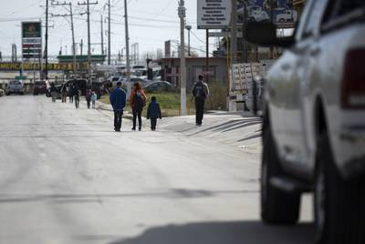 A small group of migrants walk down Libramiento Manuel Perez Treviño in Piedras Negras. The group had just left the migrant shelter. Feb. 18, 2019.