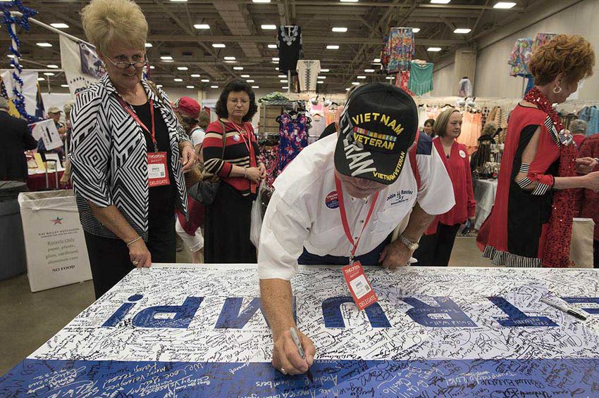Vietnam veteran Jim Faulkner of Calhoun County signs a Trump for President banner at the Republican Party of Texas event in Dallas May 13, 2016.