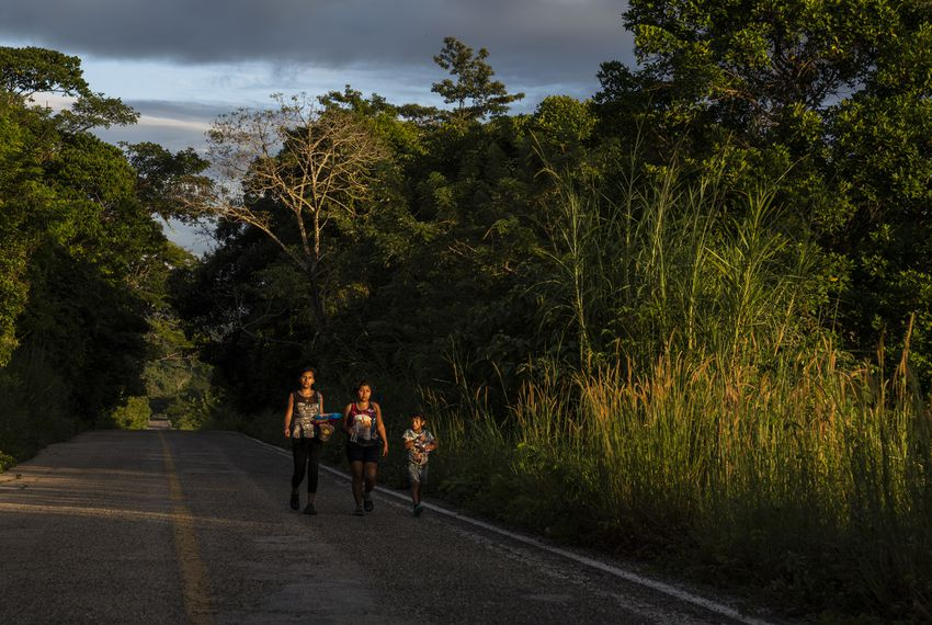 "Honduran migrants walk through Highway México 307 on Oct. 21 near Palenque, Chiapas. The highway is also known by the locals as ""El Gran Corredor del Pacífico del Migrante,"" or ""The Great Pacific Corridor of the Migrant."" This is a common route for Honduran migrants due to its proximity to their country."