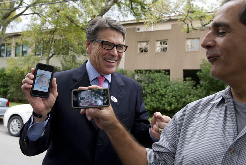 Gov. Rick Perry shows a picture of his new granddaughter to a reporter after voting early in Austin on Oct. 30, 2013.