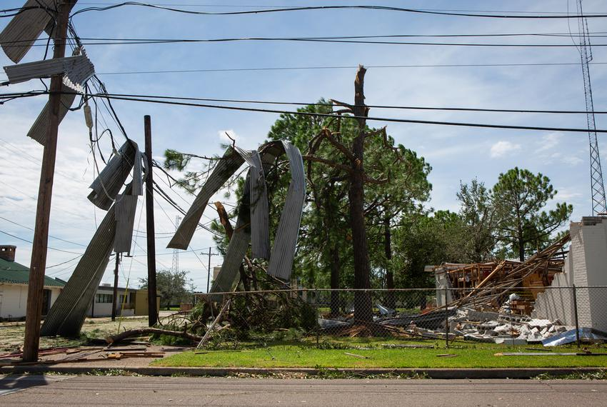 Damaged buildings, broken tree limbs and loose debris appeared all over town after hurricane-strength winds blew through O...