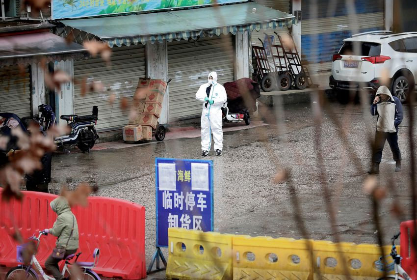 A worker in a protective suit stands near the closed seafood market in Wuhan, China.