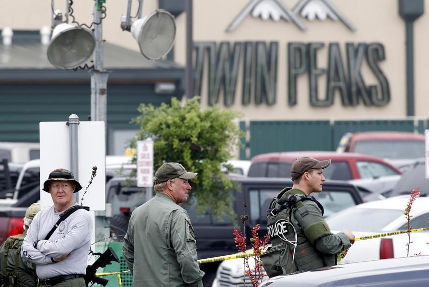 Police officers stand patrol outside of a Twin Peaks restaurant where nine members of a motorcycle gang were shot and killed…