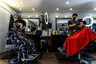 Stevin Kane and Ramiro Cruz give haircuts to customers, after Kane's Barbershop reopened from being closed due to the coronavirus pandemic.