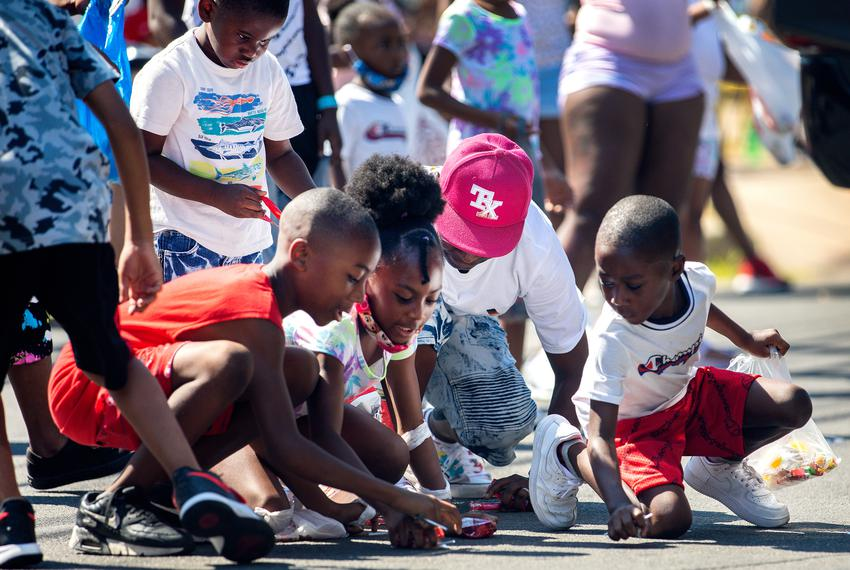 Children scramble for candy during the annual Juneteenth parade in East Austin on June 19, 2021. Juneteenth commemorates Uni…
