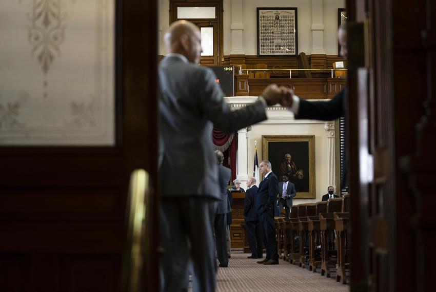 A legislator fist bumps a House Administration staffer as they entered the House Chamber on Aug. 11, 2021.