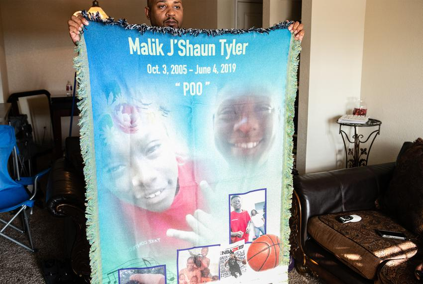 Chris White holds up a memorial blanket with pictures of Malik Tyler, a 13 year old who was killed by stray gunfire  while w…