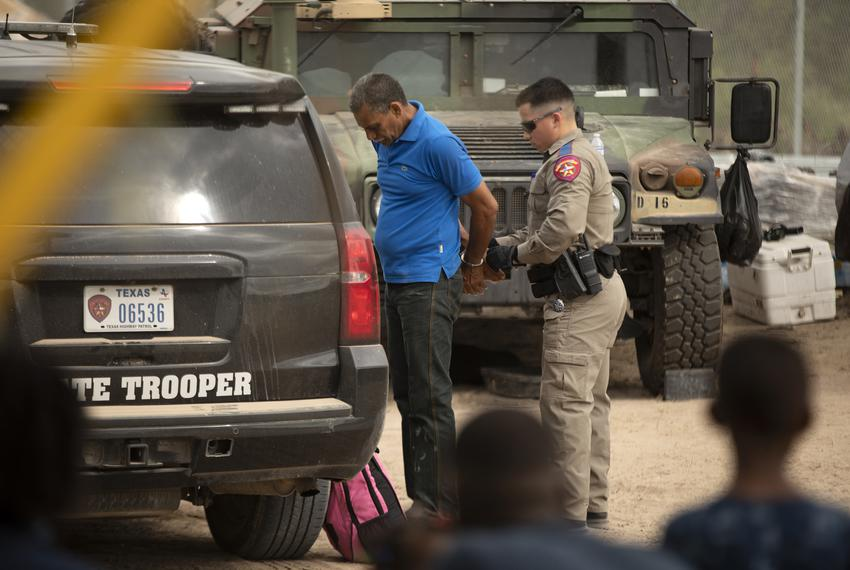A Texas Department of Public Safety official makes an arrest near the U.S. and Mexico border in Del Rio as a group of migran…