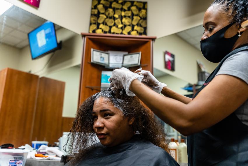 Avion Potter receives a hair relaxer treatment from hairdresser Aquita Gaddis.