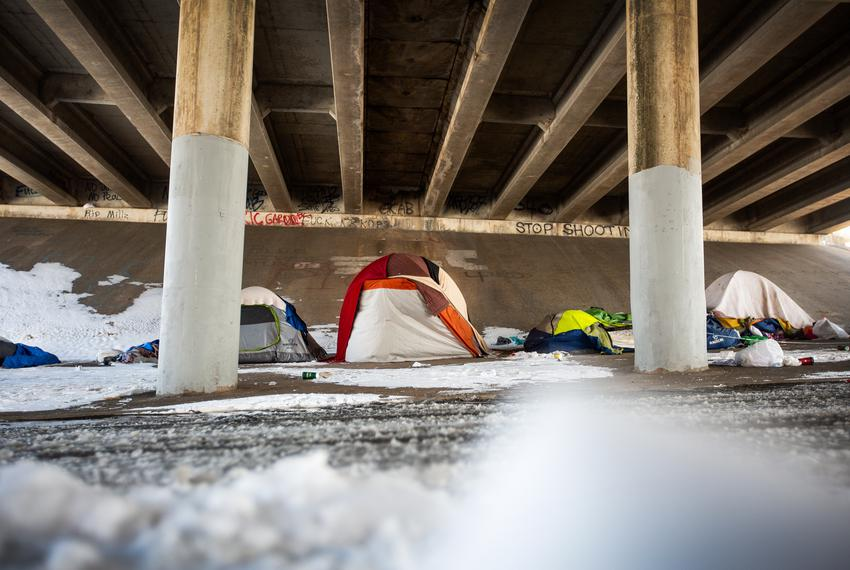 Tents sit underneath the Interstate 35 bridge on Feb. 16, 2021 in Austin.  A winter storm has caused icy roads and left mill…