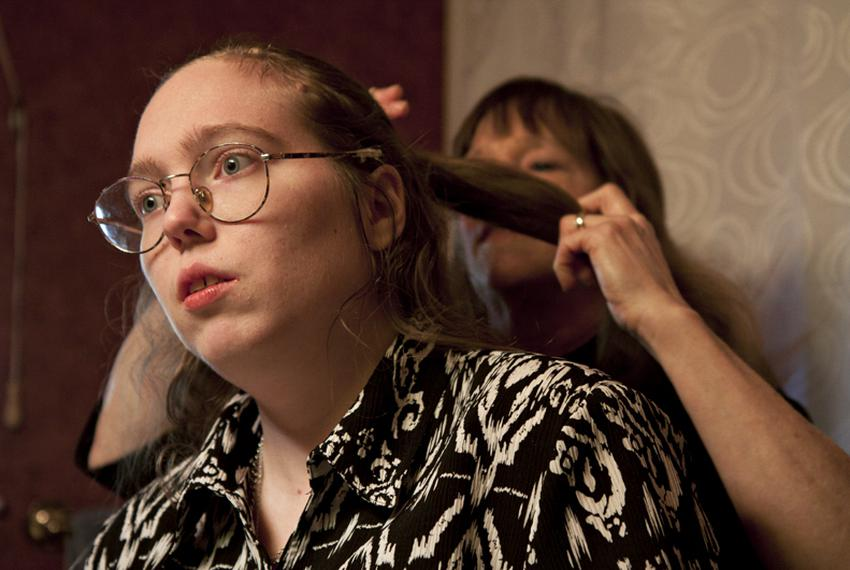 Barbara Cullison does her daughter Audrey's hair. Audrey, who is autistic, risks losing her Medicaid waiver services because…