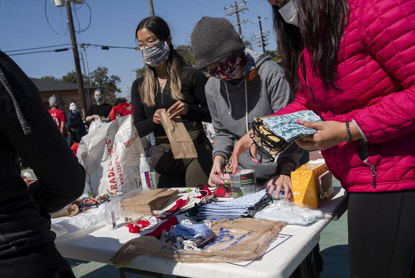 From left: volunteers Anjie Zhi, Karina Barbosa and Jessica Porras prepare masks at Kelly Village, a supply distribution sit…