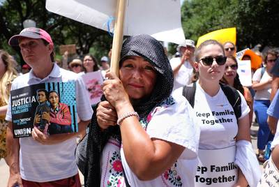 MariLu Frucduoso stands at the front of a crowd near the Capitol steps in Austin.