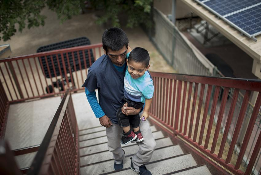 Pablo Ortiz and his 3-year-old Andres of Guatemala walk upstairs at the Annunciation House in El Paso on July 11, 2018. Orti…